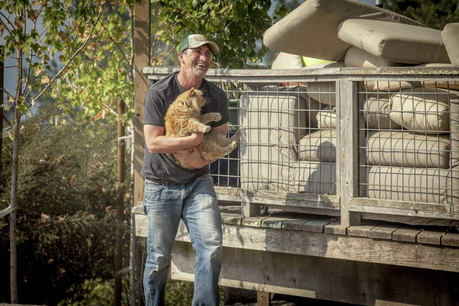 Drew Olin, retrieves his parents cat Golden who was left behind when they first evacuated from their home along Lovall Valley Rd. east of Sonoma, California, USA 14 Oct 2017. Photo: Peter DaSilva / Special To The Chronicle / ONLINE_YES