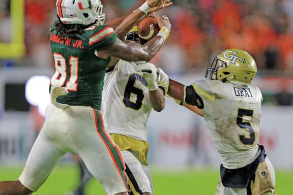 Miami's Darrell Langham, left, battles with Georgia Tech defensive backs Lamont Simmons, center, and A.J. Gray before pulling in a first-down reception on Miami's game-winning drive Saturday.