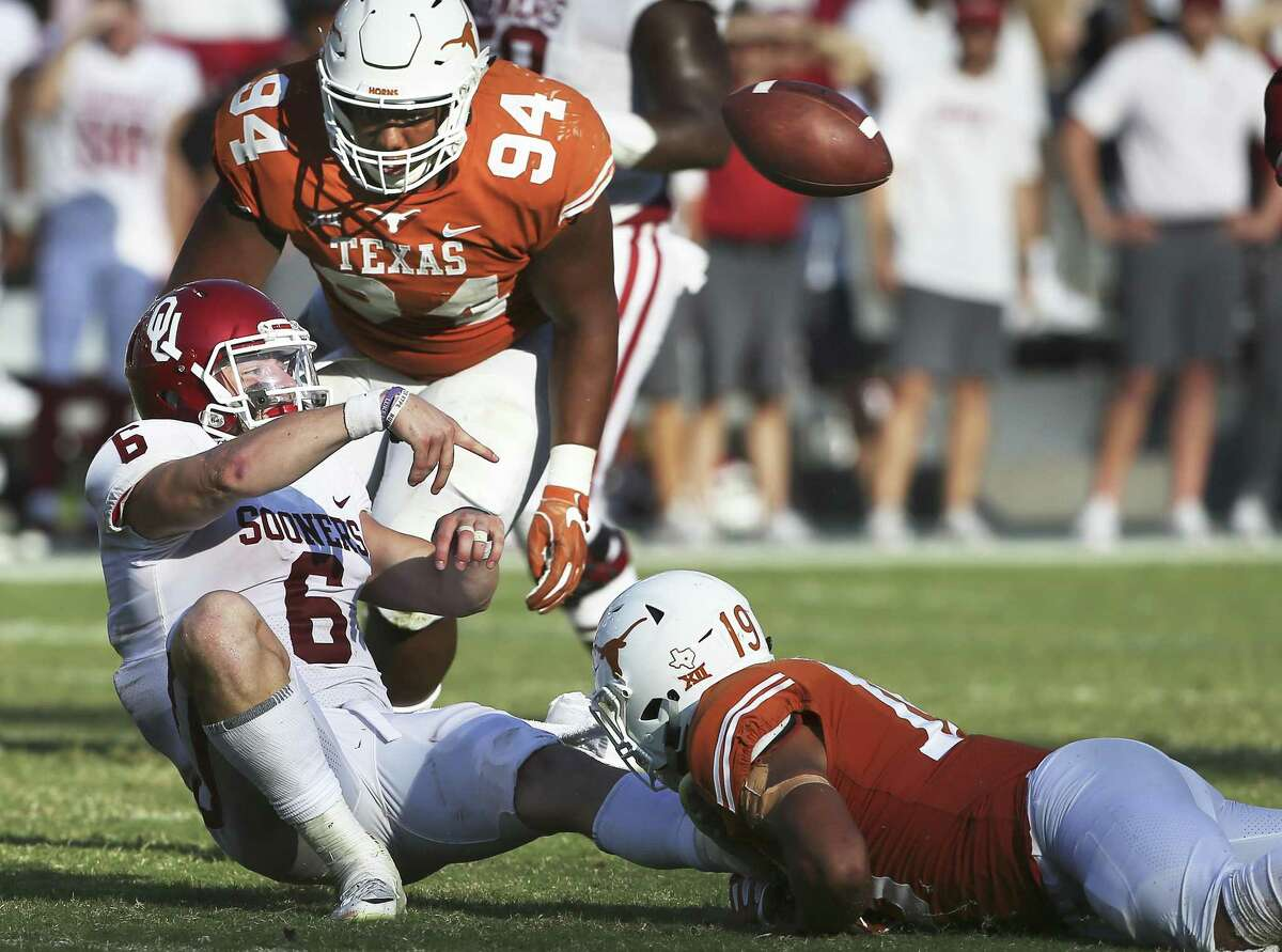 Sooner quarterback Baker Mayfield tosses a pass just before being sacked by Brandon Jones Texas plays Oklahoma in the Red River Showdown at the Cotton Bowl on October 14, 2017.