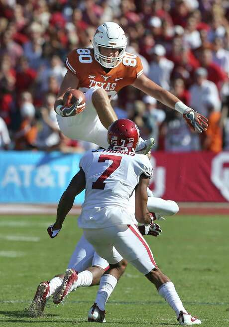 Longhorn receiver Cade Brewer jumps one tackler but runs into the next coming down after a catch in the first half as Texas plays Oklahoma in the Red River Showdown at the Cotton Bowl on October 14, 2017. Photo: Tom Reel, Staff / San Antonio Express-News / 2017 SAN ANTONIO EXPRESS-NEWS