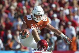 Longhorn receiver Cade Brewer jumps one tackler but runs into the next coming down after a catch in the first half as Texas plays Oklahoma in the Red River Showdown at the Cotton Bowl on October 14, 2017.