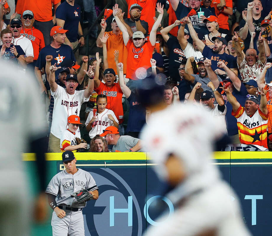 Yankees outfielder Aaron Judge walks away after failing to catch a home-run ball from the bat of the Astros' Carlos Correa, a ball that wound up in the possession of 12-year-old fan Carson Riley (standing above Judge). Photo: Brett Coomer, Staff / © 2017 Houston Chronicle