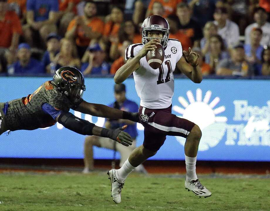 A&M quarterback Kellen Mond (11) escapes a tackle against Florida on Saturday night. Photo: John Raoux /Associated Press / Copyright 2017 The Associated Press. All rights reserved.