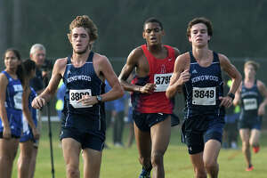 Kingwood's Carter Storm, left, and Nick Majerus, right, bookend Atascocita's Worthington Moore, center, during the Varsity Boys race at the District 21-6A Cross Country Championship at Atascocita High School on Oct. 13, 2017. (Photo by Jerry Baker/Freelance)