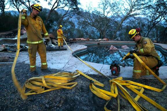 Josiah Gist (right) joins fellow Santa Cruz firefighters in using pool water in firefighting efforts at a large home that burned in The Ranch subdivision in Sonoma, Calif., on Saturday, October 14, 2017.