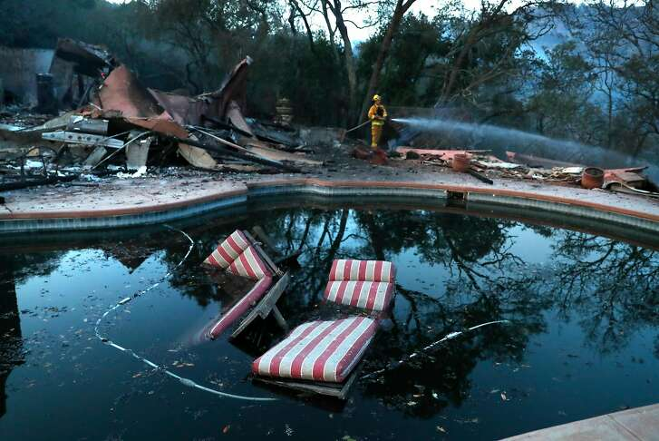Petaluma firefighter Kevin Larsen extinguishes hot spots at a large home that burned in The Ranch subdivision in Sonoma, Calif., on Saturday, October 14, 2017.