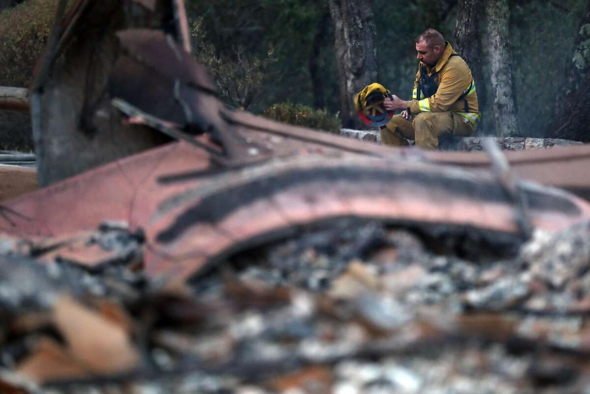 Petaluma firefighter Greg Taylor takes a break at a large home that burned in The Ranch subdivision in Sonoma, Calif., on Saturday, October 14, 2017.