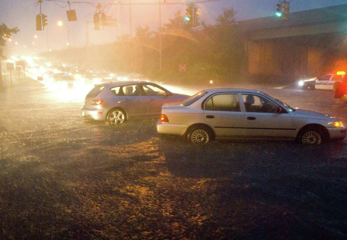 Cars battle their way through high water at the intersection of Elm and North State streets during a heavy rain storm in Stamford on Thursday, Oct. 11, 2007.