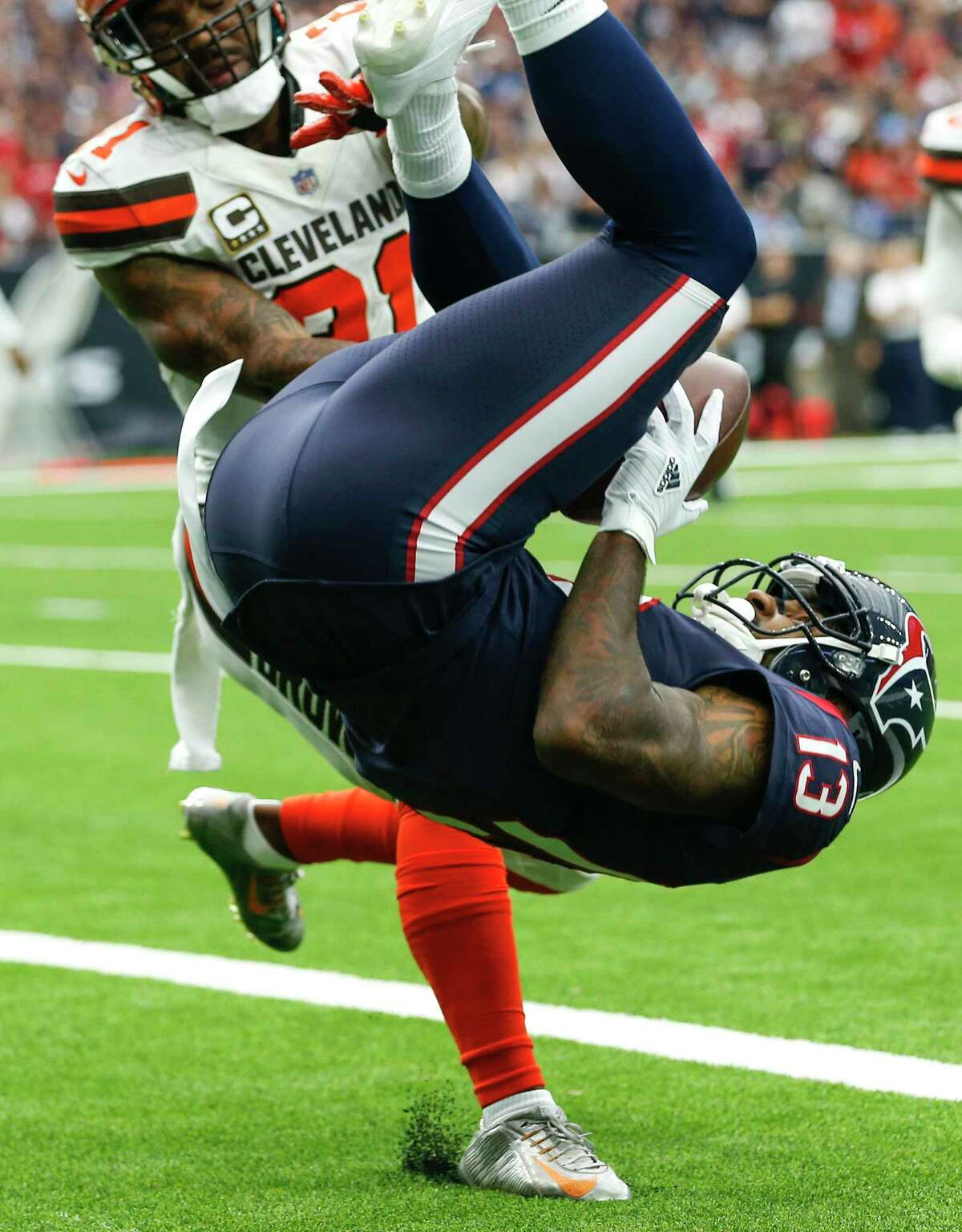 Houston Texans wide receiver Braxton Miller (13) flips into the end zone past Cleveland Browns cornerback Jamar Taylor (21) for a 1-yard touchdown reception during the second quarter of an NFL football game at NRG Stadium on Sunday, Oct. 15, 2017, in Houston.