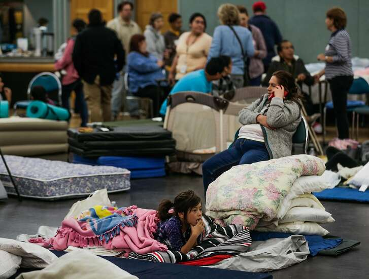 Evacuee Marta Mata, 7, (center) rests on a cot at a makeshift evacuation center while her mother Marisela Mata (right) chats on the phone after fires tore through Santa Rosa and Napa at the Petaluma Community Center in Petaluma, Calif., on Tuesday, Oct. 10, 2017.