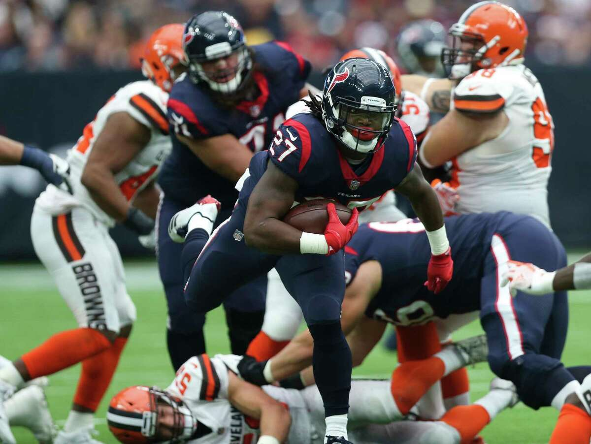 Houston Texans running back D'Onta Foreman (27) carries the ball and runs pass through a pack of Cleveland Browns players during the third quarter of an NFL football game at NRG Stadium on Sunday, Oct. 15, 2017, in Houston.