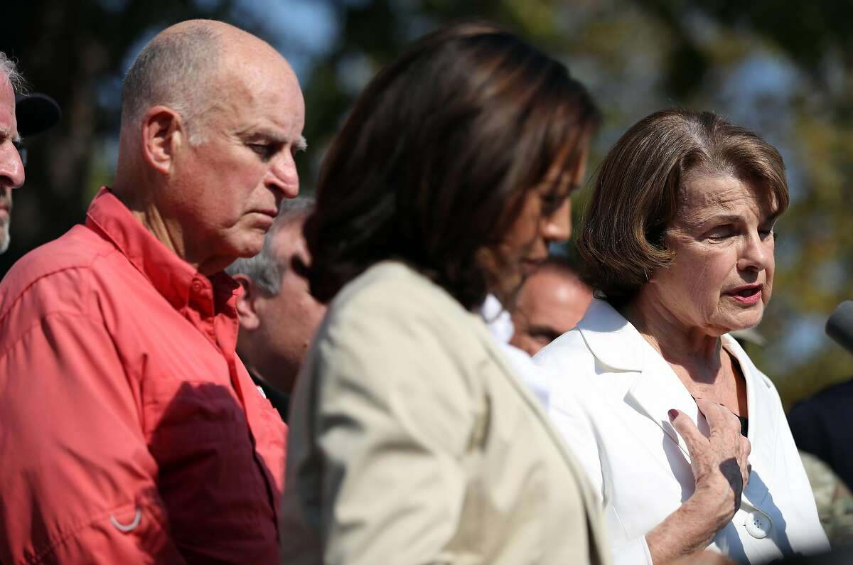 California Governor Jerry Brown and Senator Kamala Harris listen as Senator Dianne Feinstein speaks during a press conference before a Sonoma County Fire Response and Recovery community meeting at Santa Rosa High School in Santa Rosa, Calif., on Saturday, October 14, 2017. Brown vetoed legislation Sunday that would have required presidential candidates to release five years of income tax returns before their names could appear on the California ballot.