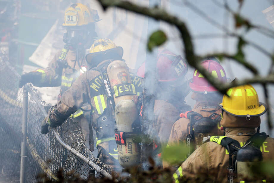 Firefighters respond to a residential fire that involved three homes on Saturday, Oct. 14, 2017, in the Shadow Bay subdivision of Willis. Photo: Michael Minasi, Staff Photographer / © 2017 Houston Chronicle