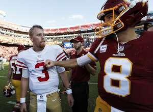 Washington Redskins quarterback Kirk Cousins (8) greets San Francisco 49ers quarterback C.J. Beathard (3) after an NFL football game in Landover, Md., Sunday, Oct. 15, 2017. The Redskins defeated the 49er 26-24. (AP Photo/Alex Brandon)