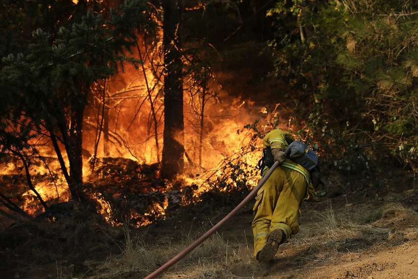 A firefighter carries a water hose to put out a fire near Calistoga on Friday. The raging fire claimed the life of Michael Dornbach, 57, who had hoped to move to the area.