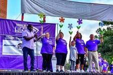 """Participants of the2017 Walk to End Alzheimer's - N. Harris/ Montgomery County, TX hold different colored flowers during the """"Promise Garden"""" ceremony. Orange represents people that support the cause and the vision of a world without Alzheimer's disease.  The purple flower represents people who have lost someone to Alzheimer's. Yellow represents people that are supporting or caring for someone with Alzheimer's and blue represents those diagnosed and living with Alzheimer's Disease."""