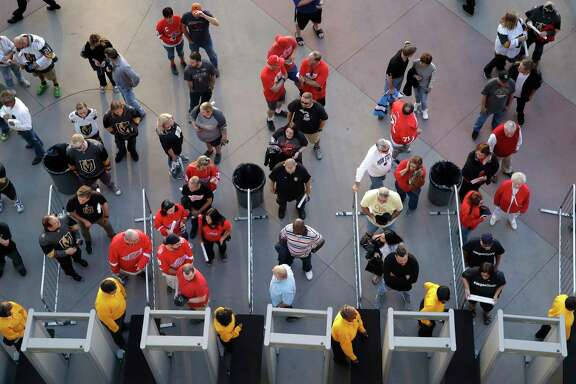 People  go through security at the T-Mobile Arena before an NHL hockey game last week in Las Vegas. Casinos and police may have to impose new security measures in the shooting aftermath.