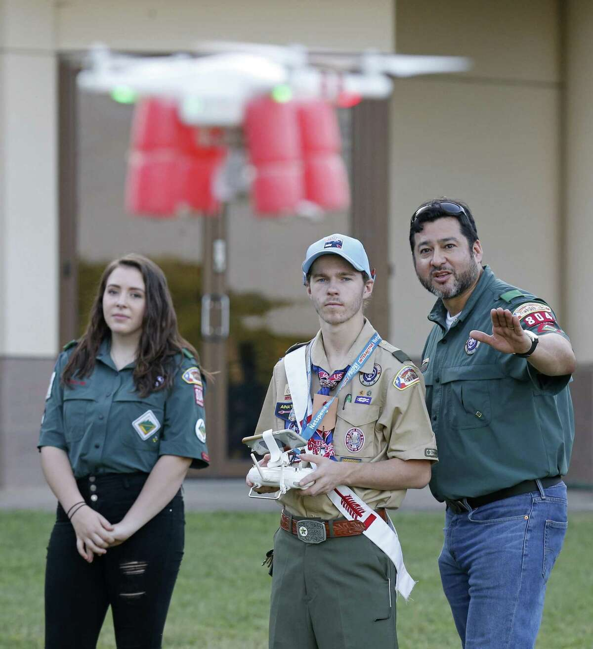 Angel Martinez III (right), a Venturing Crew 804 adviser, shows Eagle Scout Michael Chunat, 17, how to fly a drone as Crew 804 member Jenna Sealy, 15, watches. The Venture Scouts is a fully integrated program offered by the Boy Scouts.