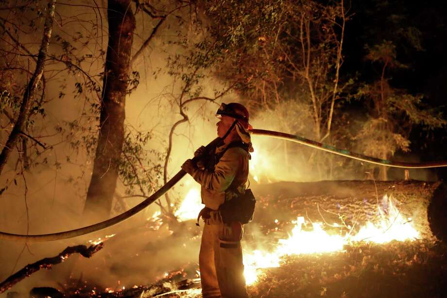 A firefighter holds a water hose while fighting a wildfire Saturday, Oct. 14, 2017, in Santa Rosa, Calif. (AP Photo/Marcio Jose Sanchez) Photo: Marcio Jose Sanchez, STF / Copyright 2017 The Associated Press. All rights reserved.