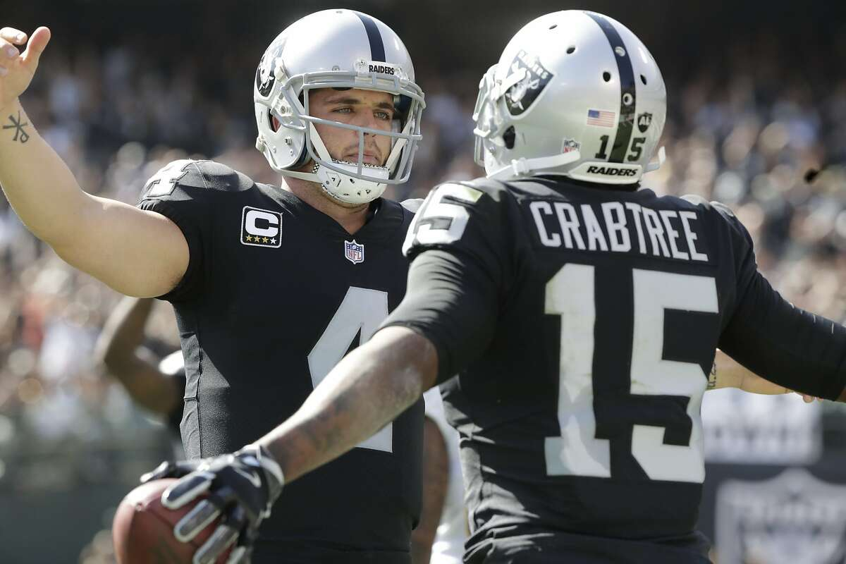 Oakland Raiders quarterback Derek Carr (4) celebrates a TD with Oakland Raiders wide receiver Michael Crabtree (15) in first quarter on Sunday, Oct. 15, 2017 in Oakland, CA.