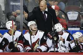 FILE - In this Sept. 22, 2017, file photo, Arizona Coyotes coach Rick Tocchet, center, gives instruction to players during the first period of a preseason NHL hockey game against the Calgary Flames in Calgary, Alberta. The rebuilt Coyotes hope the veteran Tocchet will lead the franchise back to relevance after five straight seasons of missing the playoffs. (John McIntosh/The Canadian Press via AP, File)