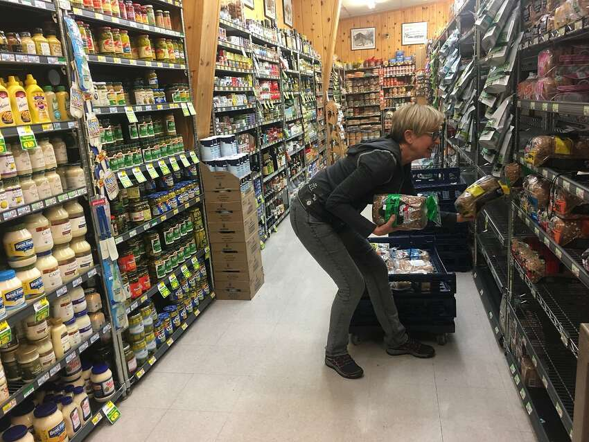 Julie Wood, the girlfriend of Calistoga Cal Mart owner Bill Shaw, helps restock the shelves shortly after the store reopened. An evacuation order was lifted Sunday.