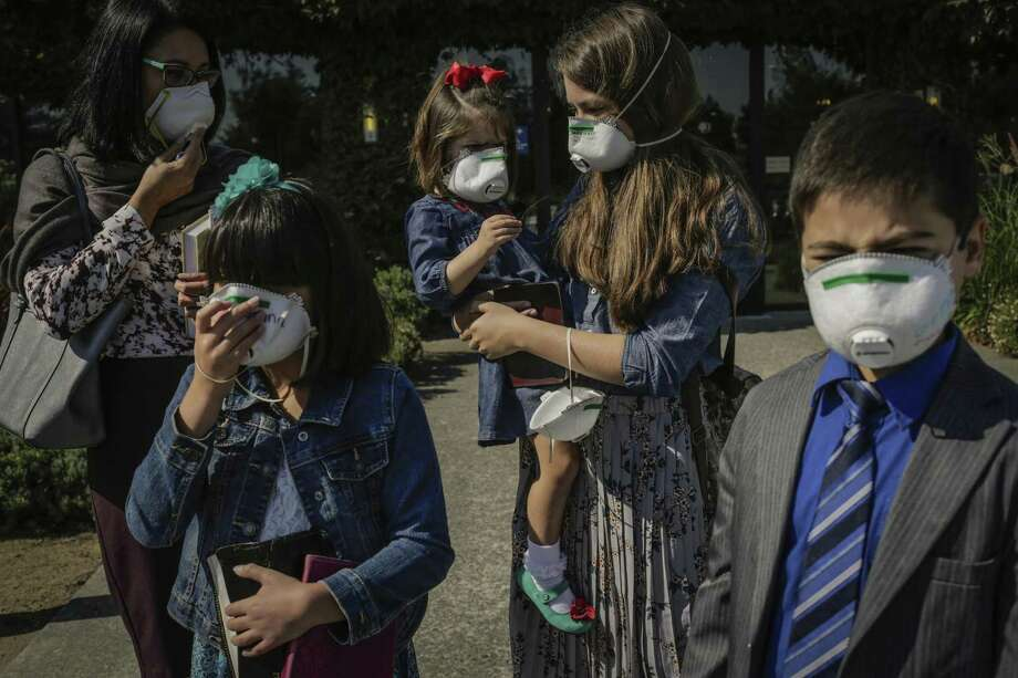 Scott family members Melody (left), Jenna, 9, Olivia, 3, being held by Kaylee, 12, and Daniel, 9, at New Hope Baptist service at the DoubleTree hotel in Rohnert Park. Photo: Gabrielle Lurie / Gabrielle Lurie / The Chronicle / ONLINE_YES