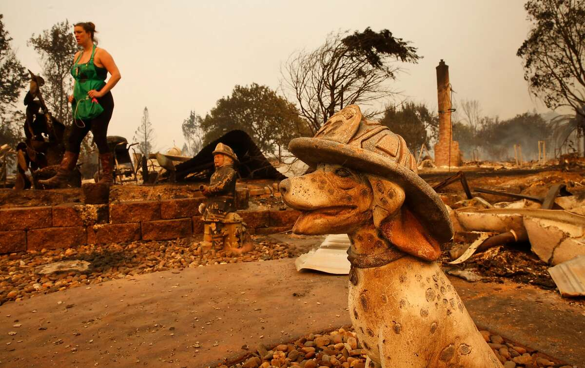 Figurines remain as Nikki Albrecht looks over her mother's home that was dstroyed in the fire, after the fire moved through the Coffey PArk neighborhood, at the scene of the Tubbs Fire in Santa Rosa, Ca., on Monday October 9, 2017. Massive wildfires ripped through Napa and Sonoma counties early Monday, destroying hundreds of homes and businesses.