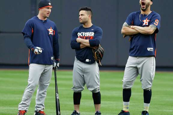 Astros third baseman Alex Bregman, left, appears to have the attention of teammate Jose Altuve, center, but Marwin Gonzalez, right, has his mind on other things during the Sunday workout.