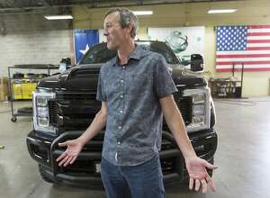 """Trent Kimball, CEO and president of Texas Armoring Corp., talks in front of a Ford """"Black Ops"""" truck at the company's San Antonio facility in this 2017 photo. Texas Armoring retro-fits custom armoring products to production vehicles. They can provide anything from light hand gun protection all the way up to armor piercing rounds protection."""