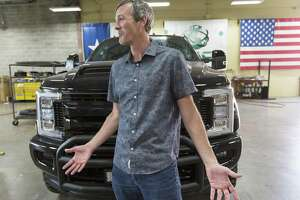 Texas Armoring Corp. CEO Trent Kimball stands in front of an armored, dual-wheeled Ford pickup truck.