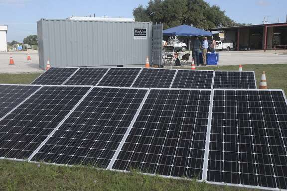 A dozen solar panels sit on the grounds of Bandera Electric Cooperative. The panels were being used to test control and safety systems within a test bed for a solar-diesel hybrid system that will be sent to a small town in Liberia.