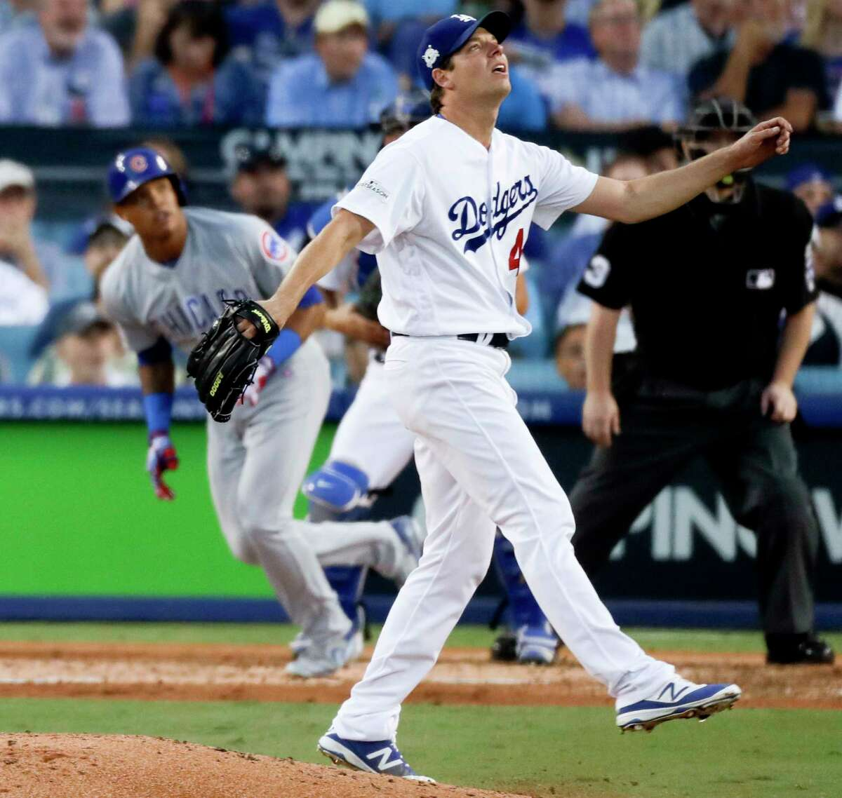 Chicago Cubs' Addison Russell, left, watches his home run off Los Angeles Dodgers starting pitcher Rich Hill during the fifth inning of Game 2 of baseball's National League Championship Series in Los Angeles, Sunday, Oct. 15, 2017. (AP Photo/Alex Gallardo)