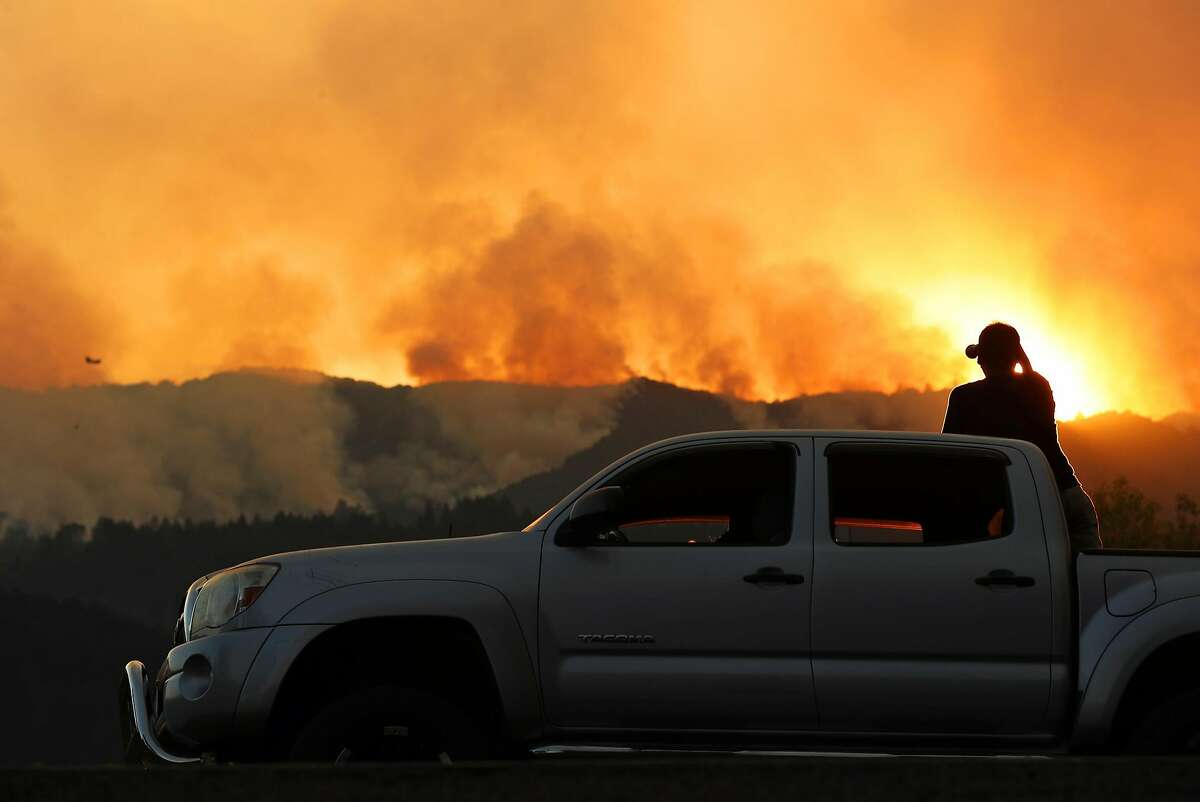 From atop his truck parked along Highway 29, Marcos Barrera of Napa watches fires burn west of St. Helena, Calif., on Sunday, October 15, 2017.
