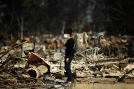 """Karen Curzon stands in what remains of her home, which was destroyed by a wildfire in the Coffey Park neighborhood, Sunday, Oct. 15, 2017, in Santa Rosa, Calif. """"We are going to rebound, rebuild and get this community back,"""" said Curzon."""