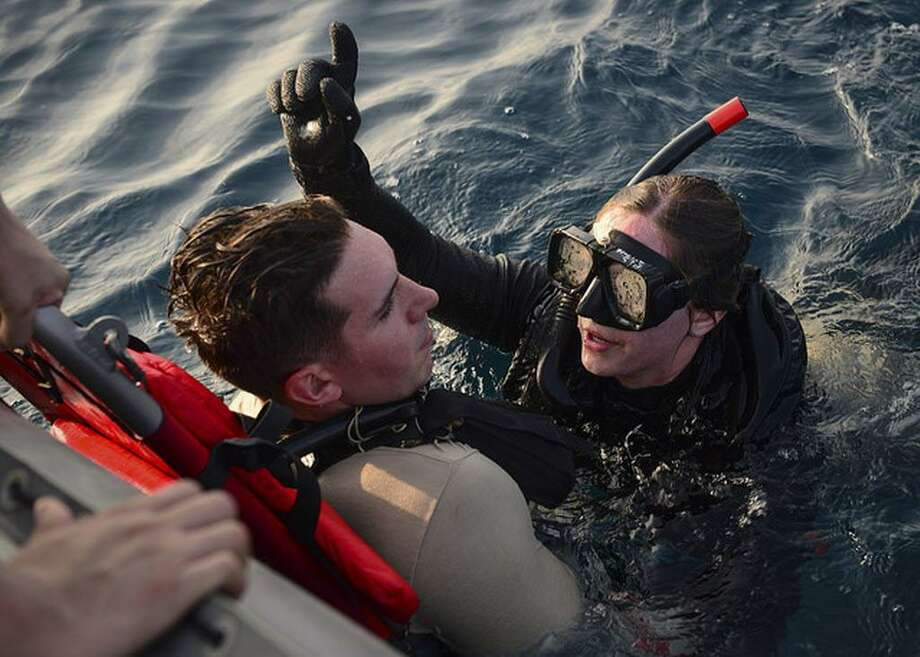 U.S. Navy Petty Officer 3rd Class Katherine Roy, right, from Middletown, raises a stretcher out of the water containing Seaman Derek Evans during a search and rescue drill with the aircraft carrier USS Nimitz in the Arabian Gulf. Photo: U.S. Navy Photo By Seaman Kennishah J. Maddux