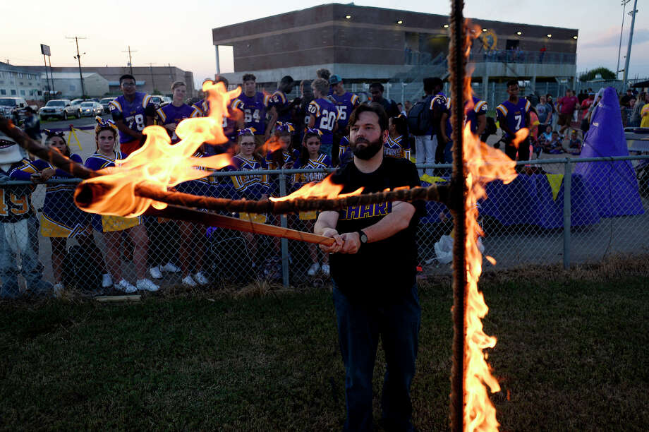 Andrew Bates, high school principal for Sabine Pass, lights the school's initials during their homecoming pep rally on Thursday. The small school's football team lost several players due to Tropical Storm Harvey.  Photo taken Thursday 10/12/17 Ryan Pelham/The Enterprise Photo: Ryan Pelham / ©2017 The Beaumont Enterprise/Ryan Pelham
