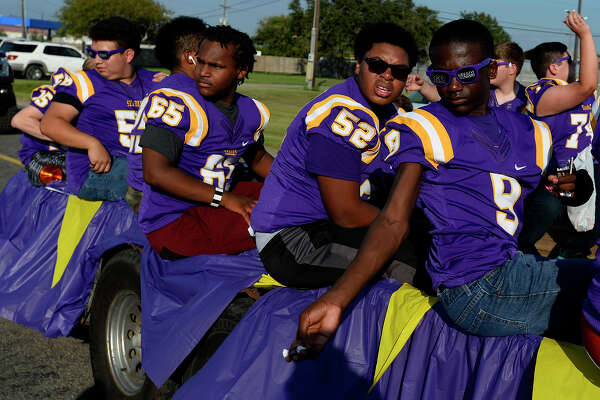 Football players toss candy to the crowd during the Sabine Pass homecoming parade on Thursday. The small school's football team lost several players due to Tropical Storm Harvey. Photo taken Thursday 10/12/17 Ryan Pelham/The Enterprise