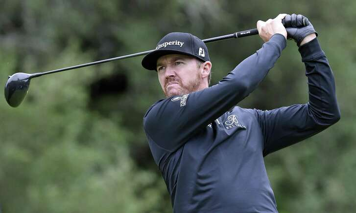 Jimmy Walker grimmaces as he hits his drive into a stiff wind on the 9th teebox during the third round of the Valero Texas Open at TPC San Antonio Oaks Course on April 22, 2017.