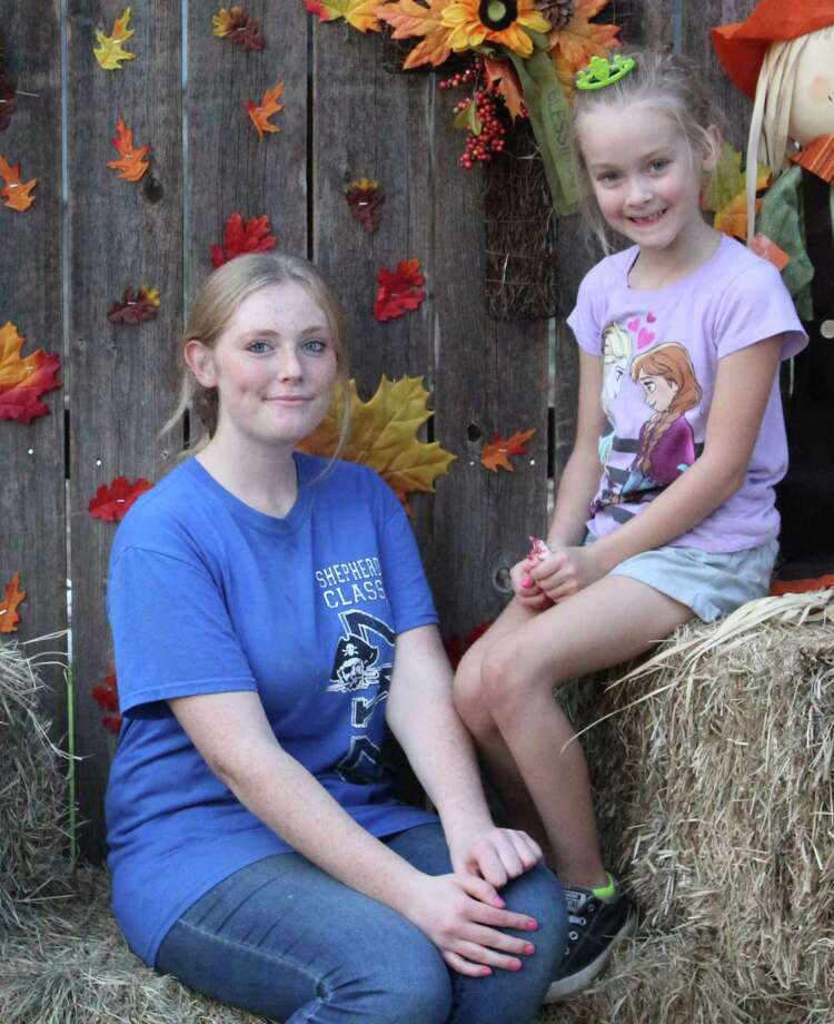 Kara (left) and Madison Cooper (right) pose near a display setupfor pictures at the Impact Center's grand opening. Photo: Jacob McAdams