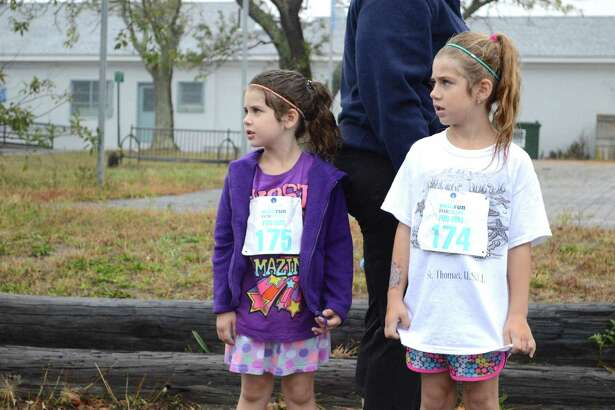 Hair wet but spirits not dampened, stand Kaleigh Doll, 5, left, and her sister Gianna, 6, of East Hampton, at the 11th annual Walk-Run for Hope fundraiser for CancerCure, held at Jennings Beach on Sunday, Oct. 15, 2017, in Fairfield, Conn.