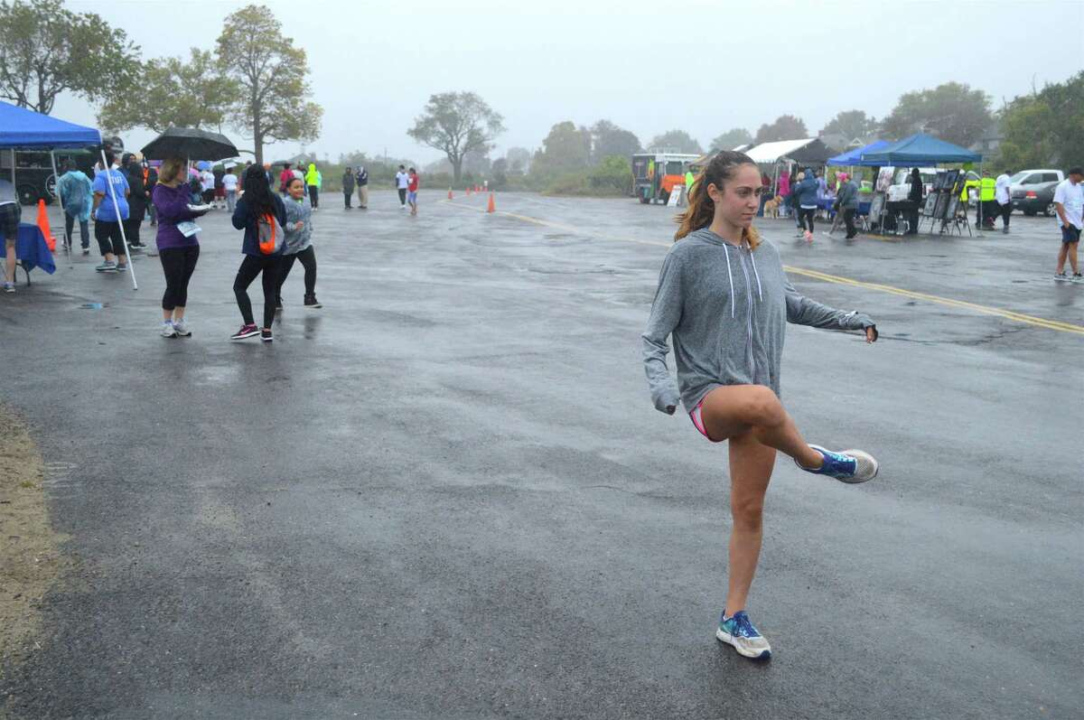 Lila Miller, 14, of Weston, warms up to run at the 11th annual Walk-Run for Hope fundraiser for CancerCure, held at Jennings Beach on Sunday, Oct. 15, 2017, in Fairfield, Conn.