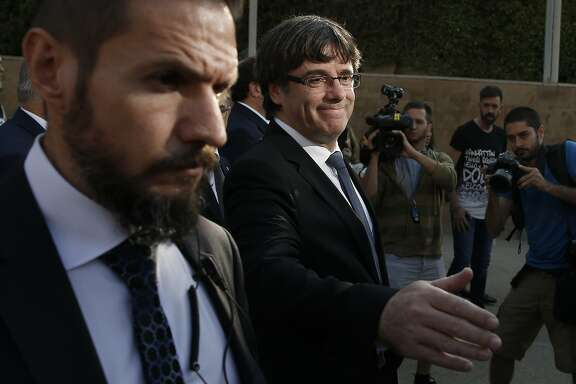 Catalan regional President Carles Puigdemont gestures after a ceremony commemorating the 77th anniversary of the death of Catalan leader Lluis Companys at the Montjuic Cemetery in Barcelona, Spain, Sunday, Oct. 15, 2017. Catalonia's separatist movement is being threatened by infighting over strategy to culminate its long-held desire to break away from Spain. Die-hard separatists are pushing for a definitive declaration of independence in the next few days. (AP Photo/Manu Fernandez)