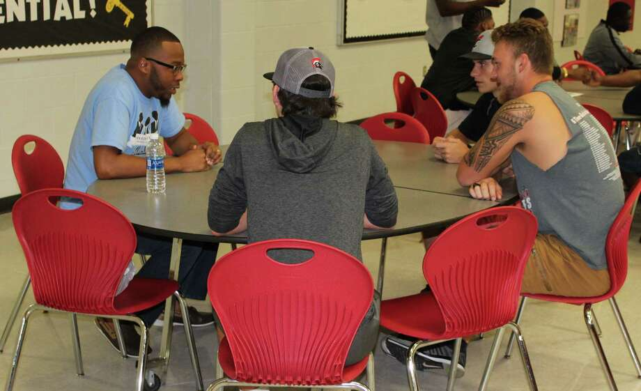 Brandon Roberts (left) of the Distinguished Gentlemen discusses individuality, choices, decisions, leadership, presentation and confidence with a group of Coldspring-Oakhurst High School Trojan football players during the Homecoming Impact Breakfast on Oct. 14. Photo: Jacob McAdams