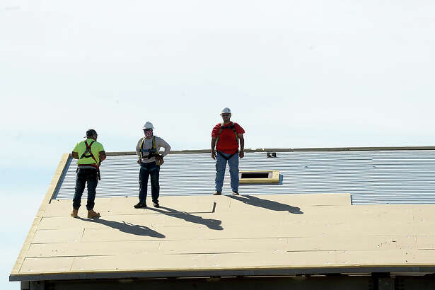 Construction crews lay down roofing as building continues on the Fire Station #1 facility on Gulf Avenue in Beaumont. Work is getting back on track after delays caused by Harvey that effected a number of the workers, as well as ability to continue during the heavy rains. Crews are expected to begin brick work this week. Photo taken Monday, October 16, 2017 Kim Brent/The Enterprise