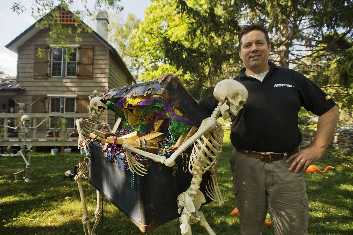 Rich Marshall poses for a photo among the elaborate Halloween-themed display on their front lawn on Ashman Street. Rich is responsible for the decorations on the outside of their home, while his wife Karen has decorated the interior for the Halloween season. (Katy Kildee/kkildee@mdn.net)