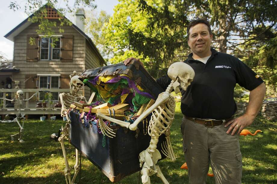 Rich Marshall poses for a photo among the elaborate Halloween-themed display on their front lawn on Ashman Street. Rich is responsible for the decorations on the outside of their home, while his wife Karen has decorated the interior for the Halloween season. (Katy Kildee/kkildee@mdn.net) Photo: (Katy Kildee/kkildee@mdn.net)