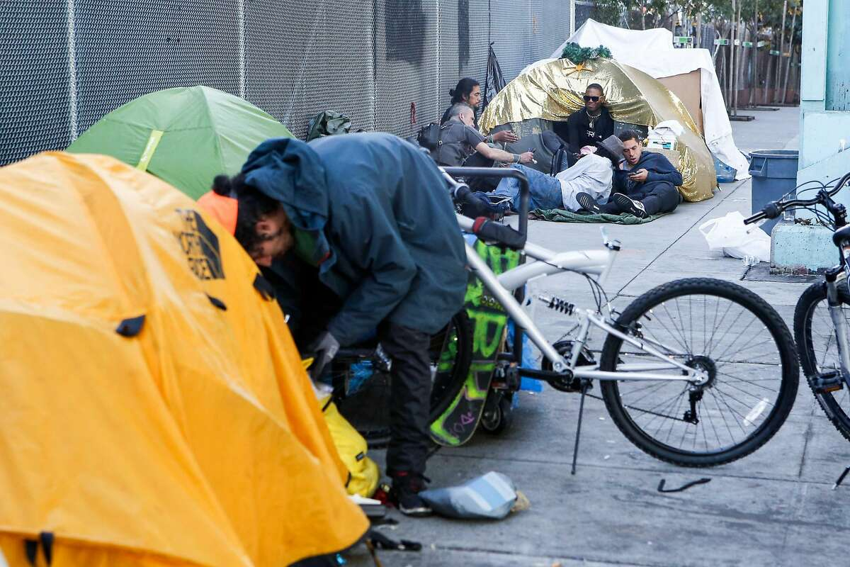 Residents of a tent encampment on Duboce Ave hang out near their tents on October 15, 2017 in San Francisco, Calif.