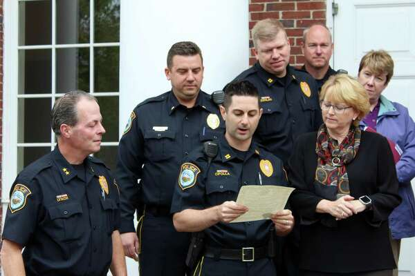 Wilton Police Capt. Rob Cipolla reads the town proclamation designating October as Domestic Violence Awareness Month in front of Town Hall on Monday, Oct. 16, 2017.
