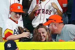 Carson Riley (left) his mother Amanda and dad Mike react to Carlos Correa's home run that Carson nearly caught in front of Yankees right fielder Aaron Judge in the fourth inning of Game 2 of the ALCS at Minute Maid Park on Saturday, Oct. 14, 2017, in Houston. ( Brett Coomer / Houston Chronicle )